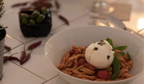 Pasta with burrata on a table with olives on the side